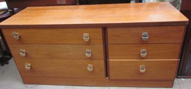 A teak chest of drawers with an arrangement of six drawers