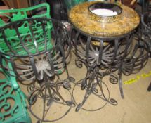 A pair of black painted scrolling metal pot stands together with a smaller example and a lacquer