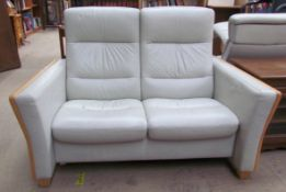 A green leather and beech upholstered two seater settee together with a pair of elbow chairs and