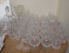 A suite of crystal drinking glasses including champagne glasses, brandy balloons, whisky tumblers,