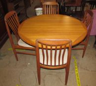 A mid 20th century teak extending dining table and four chairs,