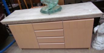 A modern sideboard with a reconstituted marble top,