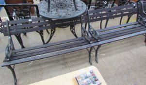 A set of three cast iron and wooden slatted garden benches