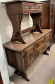 A 20th century Gothic style oak sideboard with a rectangular planked top above two central drawers