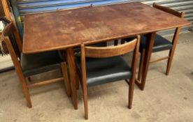 A mid 20th century teak extending dining table on tapering legs together with a set of four teak