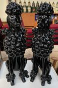 A pair of large model seated poodles in gloss black