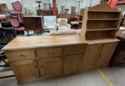 A small pine dresser the shaped back above two shelves and two cupboards on a plinth base,