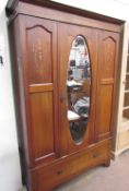 An Edwardian mahogany wardrobe, the moulded cornice above a central oval mirrored door,