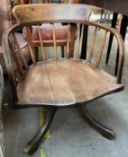 A 19th century horse shoe shaped chair with a spindle back and solid seat on a splayed base