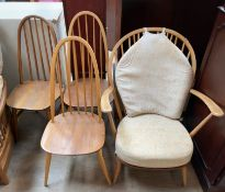 An Ercol elbow chair together with a set of three spindle back dining chairs