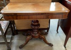 A Victorian mahogany card table the rectangular hinged top with rounded corner with a baize