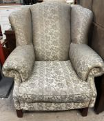 A George III style wing back upholstered arm chair on square legs
