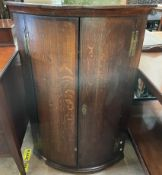 A mid 18th century oak hanging corner cupboard with a pair of mahogany crossbanded doors,