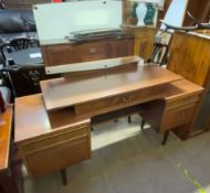 A mid 20th century teak dressing table with an arrangement of drawers on tapering legs