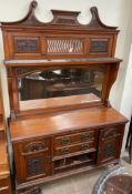 An Edwardian walnut mirrorback sideboard, with a carved cresting, shelf and arched mirror,