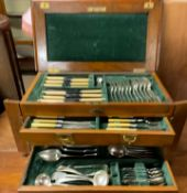 An electroplated part flatware service contained in an oak box with a hinged top and three drawers