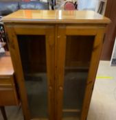 A modern pine side cabinet with a pair of glazed doors