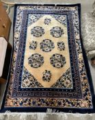 A Chinese rug with a golden ground and circular scrolling floral decoration to blue bands