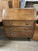 A 19th century oak bureau, the sloping fall enclosing a fitted interior of pigeon holes and drawers,