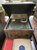 An oak cased HMV table top gramophone with a book and collection of records