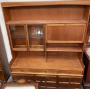 A teak wall unit, with shelves and glazed cupboards,