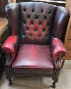 A red leather upholstered wing back chair on cabriole legs