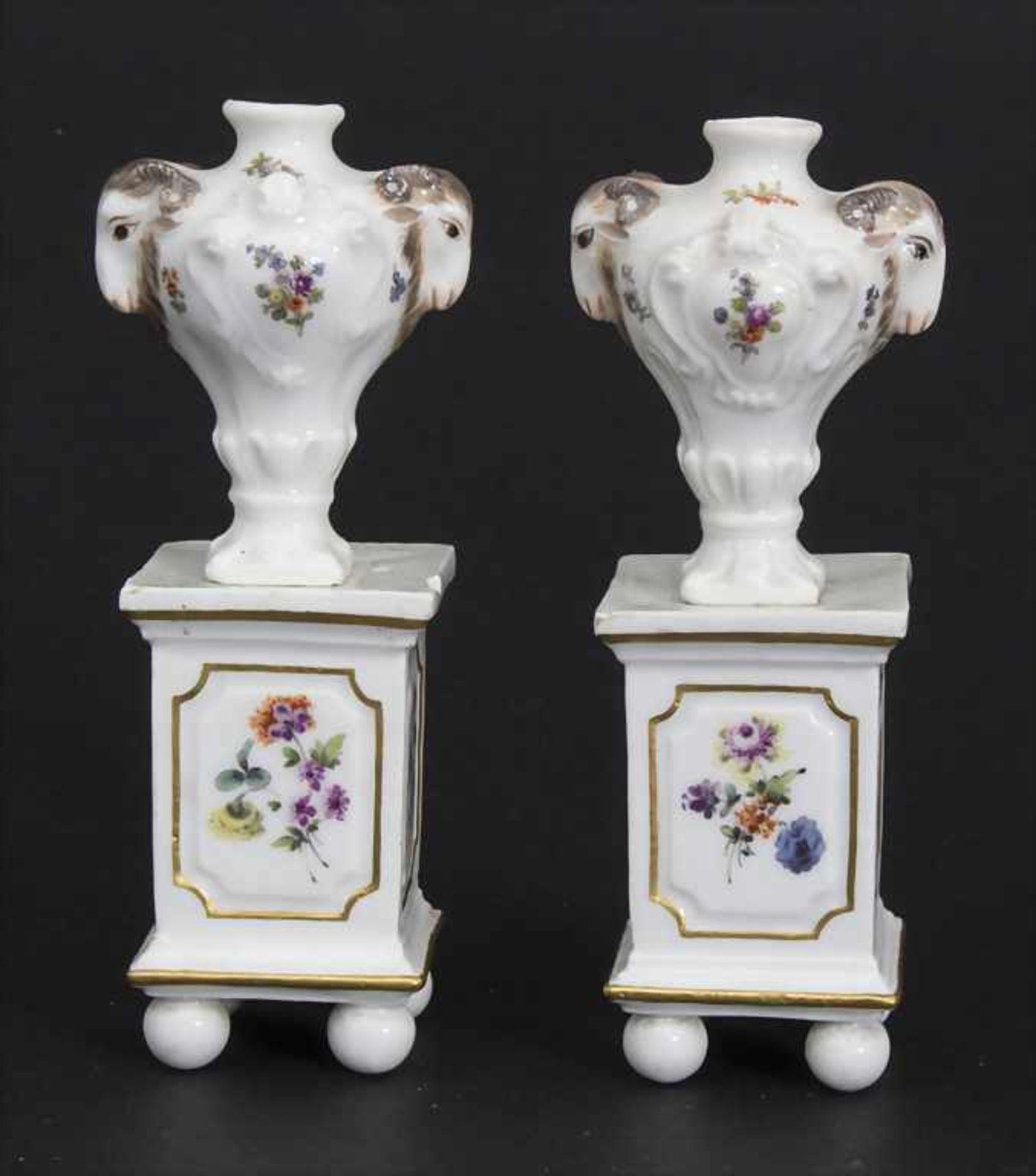 Paar Miniatur Vasen mit Widderköpfen auf Postamenten / A pair of miniature vases with ram heads on