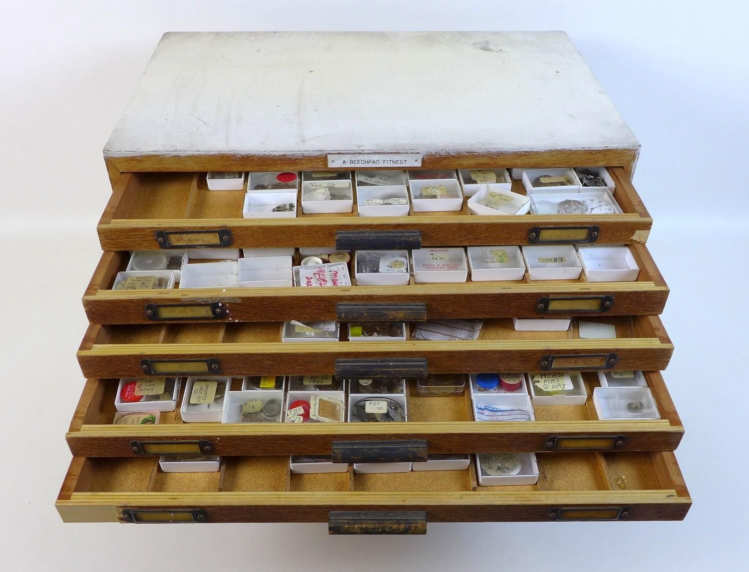 Lot 92 - A collection of watch parts, contained within an oak ten drawer table top chest