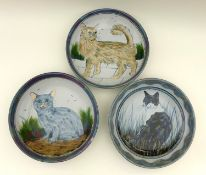 A group of Highland Stoneware pottery, comprising three large bowls each depicting cats, two signed,