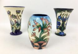 Three Moorcroft pottery vases, comprising two vases of tapering form, one in violet pattern with