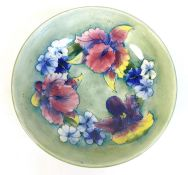 A Moorcroft bowl, the pale green ground decorated with Irises and blue violas, tublined and painted,