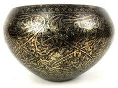 A 19th century Persian brass niello bowl, profusely decorated with Arabic calligraphic script