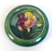 A Moorcroft lipped trinket bowl, tube line and painted, decorated with lillies, impressed