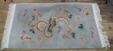 A washed Chinese rug, with a dragon on a