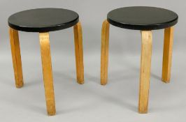 Attributed to Alvar Aalto, a pair of stacking stools, with circular black seats, 44cm high.