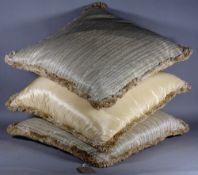 A group of three modern part silk cream and gold cushions, each 62cm wide.