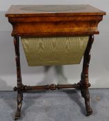 A late Victorian walnut work table with oval inset leather top on turned supports,