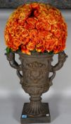 A Victorian style composite faux cast iron twin handled urn with an arrangement of dried orange