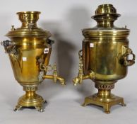 A Russian brass samovar with twin handles and tap, 51cm high and another similar brass samovar, (2).