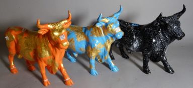 A group of three 20th century painted composite figures of a bull, each individually painted,