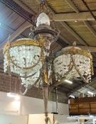 A French gilt metal and cut glass chandelier, modelled as a torch flanked by three baskets,
