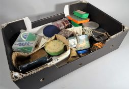 A large fruit box with a tackle box and lures, fly boxes, fly lines and further fishing items,
