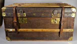 An early 20th century leather and wooden bound trunk with brass mounts, 81cm wide x 40cm high.