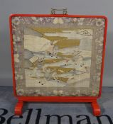 A Chinese silk work panel within a red metal frame.