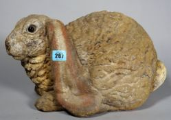 A 20th century painted stone rabbit, 38cm wide x 24cm high.