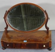 A late Victorian mahogany toilet mirror with three frieze drawers, on bun feet,