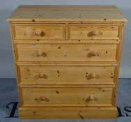 A 20th century pine chest of two short and three long graduated drawers, resting on a plinth base,