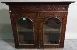 An early 20th century rosewood display cabinet with arch panelled glass doors and carved decoration,