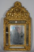 A 19th century gilt brass and bevelled glass cushion shaped wall mirror, 32cm wide x 49cm high.