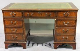 A 20th century hardwood pedestal desk with nine drawers about the knee,
